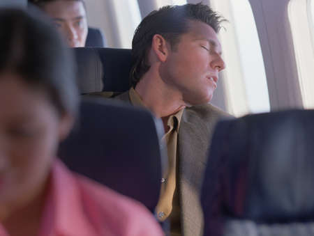Man sleeping in an airplane LANG_EVOIMAGES
