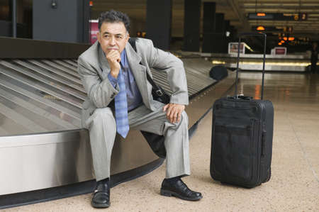 Businessman sitting on a conveyor belt at an airport