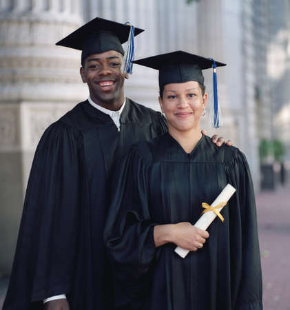 Young male and female graduate standing together outdoors smiling LANG_EVOIMAGES