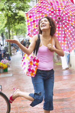 Young woman holding an umbrella laughing in the rain LANG_EVOIMAGES