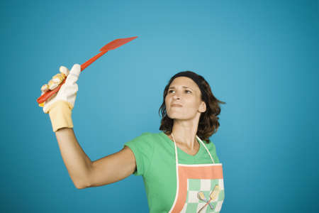 Woman in apron with fly swatter LANG_EVOIMAGES