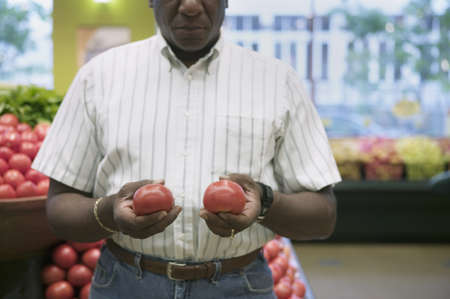 Elderly man standing at a supermarket holding vegetables
