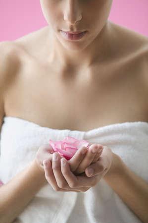 Contemplative teen girl holding rose petals