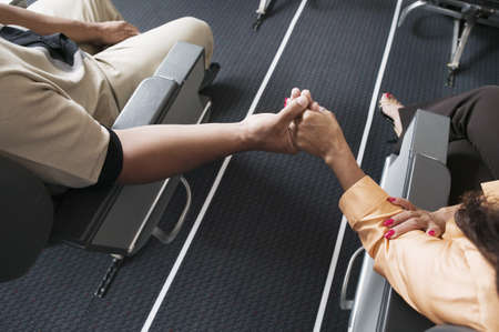 High angle view of a mid adult couple holding hands across the isle in an airplane