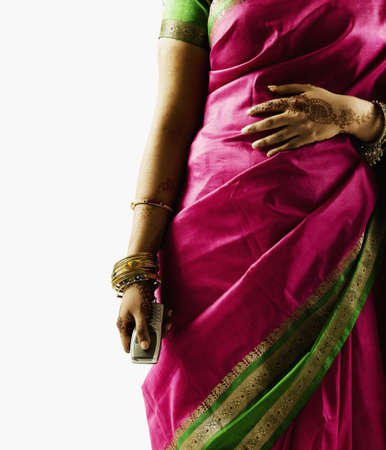 Torso of a woman in a sari holding a mobile phone LANG_EVOIMAGES