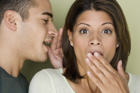 Man whispering into womanís ear