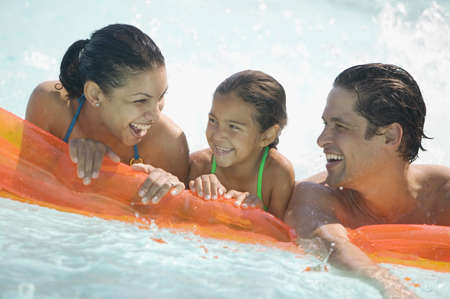 Young couple and their child resting on an air mattress smiling