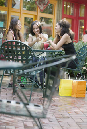 Young women sitting together having lunch in mall