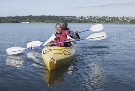 Elderly couple kayaking together on a lake