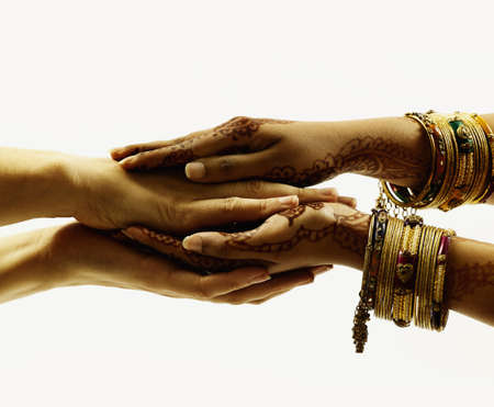 Two pairs of human hands clasped together LANG_EVOIMAGES