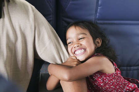 Young girl holding a mans arm sitting in an airplane