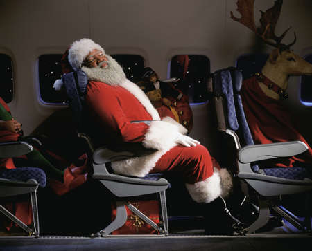 Santa clause sleeping in an airplane seat