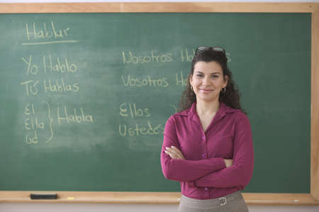 Portrait of mid adult female teacher standing in front of a classroom