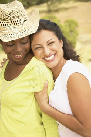 Portrait of two young woman holding each other smiling