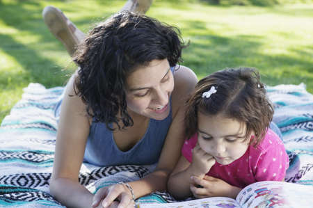 Mother and her daughter lying on a lawn reading a book