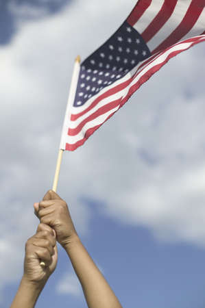 Persons hands holding up an American flag LANG_EVOIMAGES