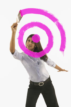 Young woman painting circles on glass