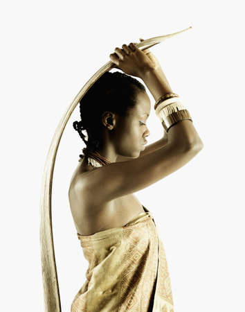 Side profile of a young tribal woman standing holding a wooden stick over her head