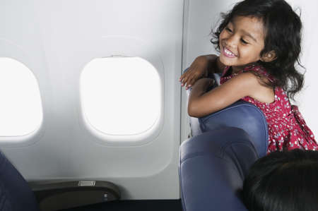 Young girl standing on the seat looking back in an airplane