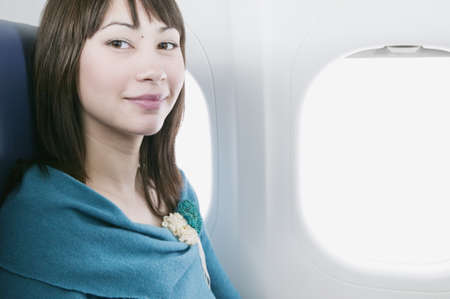 Portrait of a young woman traveling in an airplane