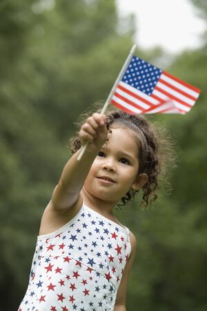 Young girl holding up an American flag LANG_EVOIMAGES