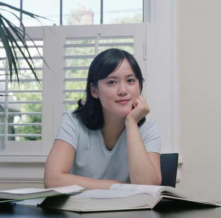 Young woman sitting at a desk looking at camera