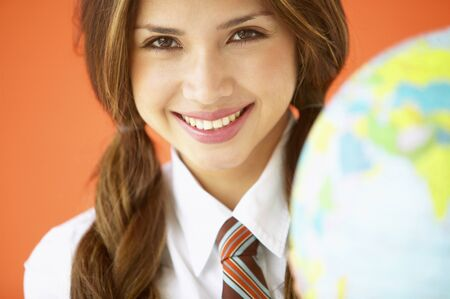 Portrait of young woman smiling holding a globe LANG_EVOIMAGES
