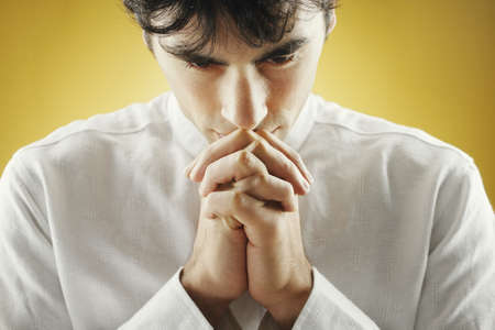 Closeup of young man praying LANG_EVOIMAGES