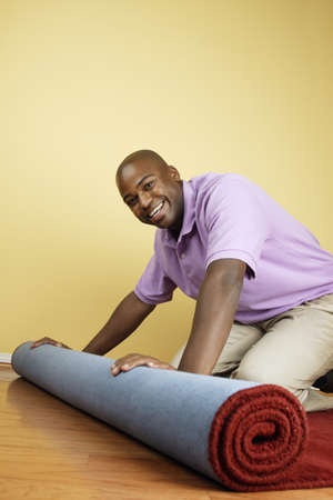 Portrait of a young man rolling up carpet