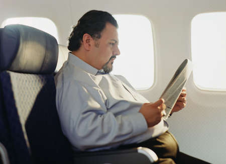 Man sitting in an airplane reading a newspaper