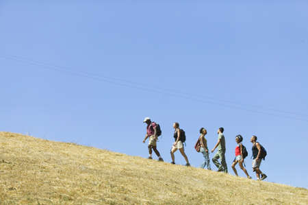 Group of hikers walking uphill LANG_EVOIMAGES