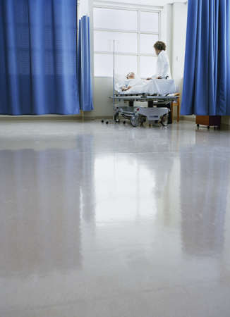 Medical professional standing besides a patients bed in a hospital LANG_EVOIMAGES