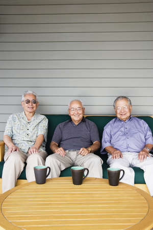Portrait of three elderly men sitting on couch drinking coffee