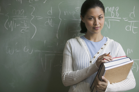 Young woman holding backs standing in a classroom