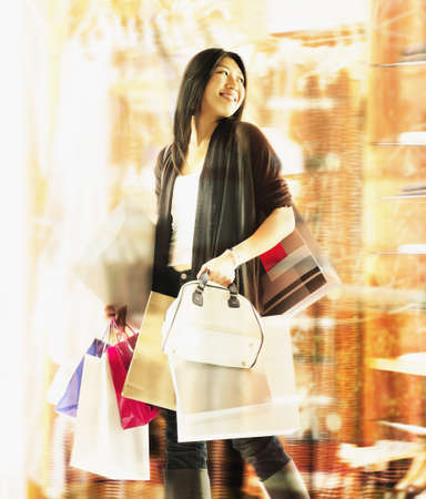 Young woman standing holding shopping bags LANG_EVOIMAGES