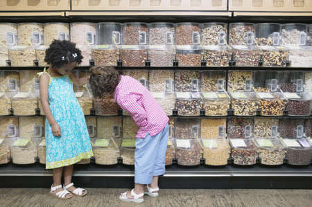 Children at a supermarket looking at assorted nuts stored in bulk food bins LANG_EVOIMAGES
