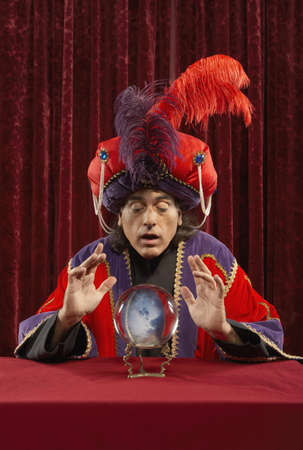 Magician with feather hat leaning over crystal ball