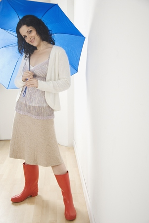 Portrait of woman with umbrella and rubber boots