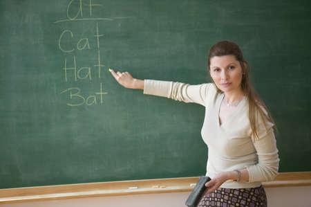 Portrait of female teacher point to words on chalkboard LANG_EVOIMAGES
