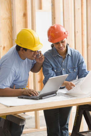 Two construction workers looking at plans while using cell phone and laptop