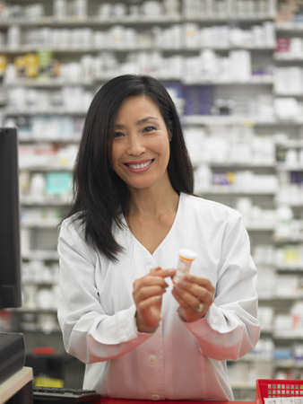 Female employee displaying a bottle of pills for the camera LANG_EVOIMAGES