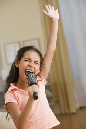 Young girl singing into a hairbrush LANG_EVOIMAGES