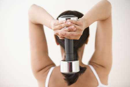 Rear view of woman exercising with dumbbell behind head