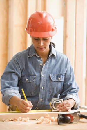 Female construction worker measuring wood with tape measure LANG_EVOIMAGES