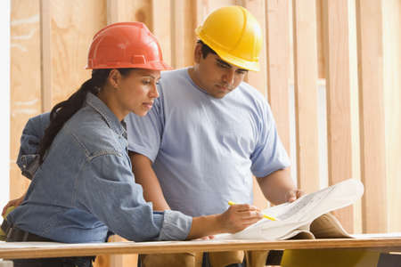 Two construction workers studying plans
