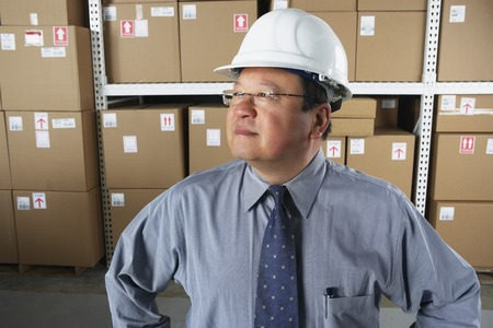 Middle-aged Asian businessman wearing hard hat in warehouse