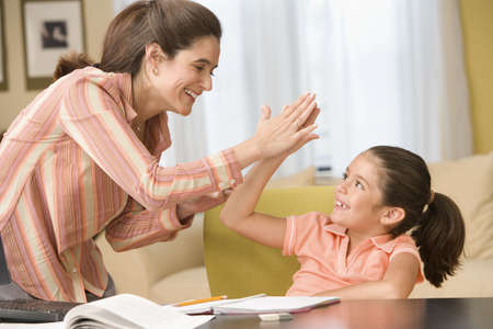 Mother giving daughter high five LANG_EVOIMAGES