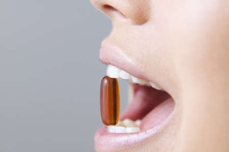 Young woman holding a pill between her teeth