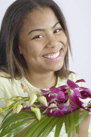 Teenage girl holding a bunch of purple flowers LANG_EVOIMAGES