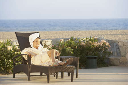 Woman in lounge chair at beach hotel, Los Cabos, Mexico LANG_EVOIMAGES